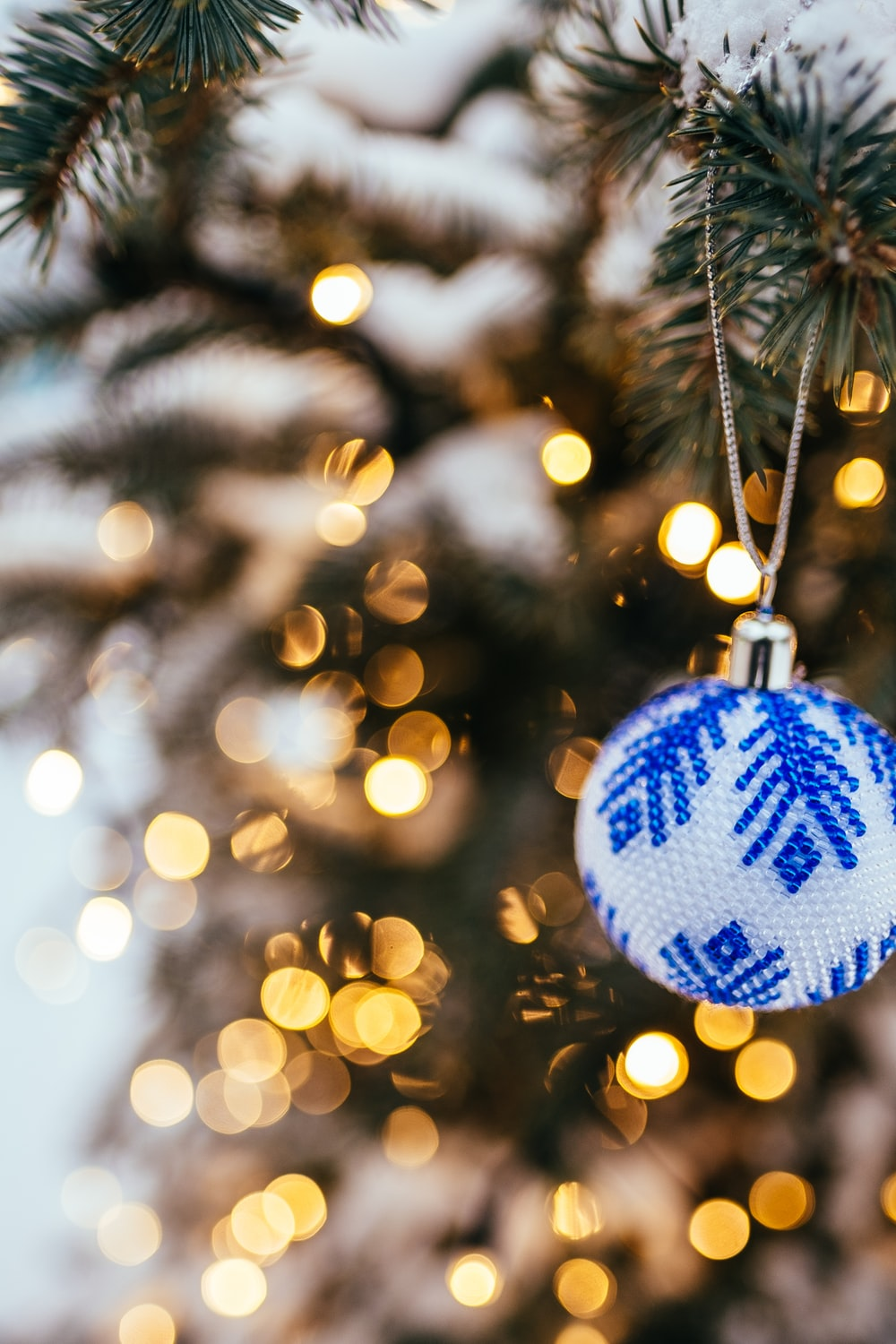 blue and white bauble hanging on christmas tree in bokeh photography
