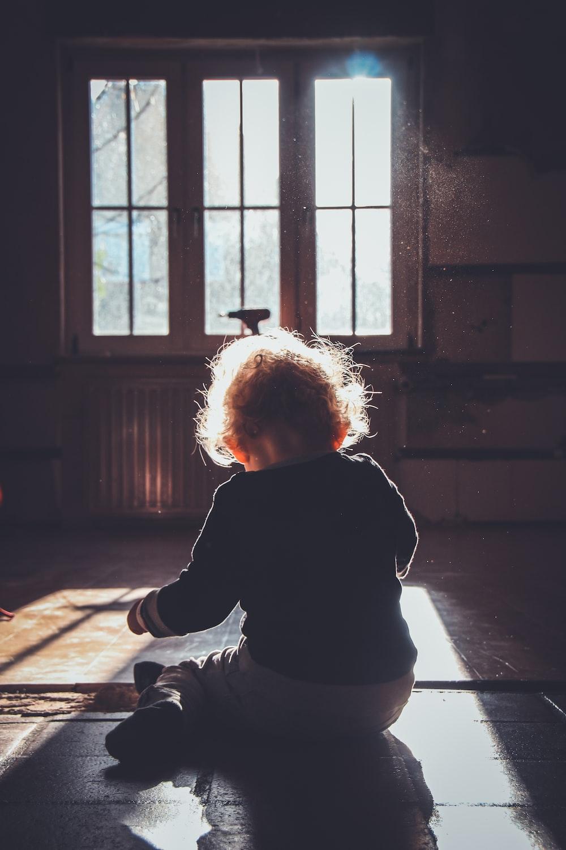 toddler sitting on brown wooden floor