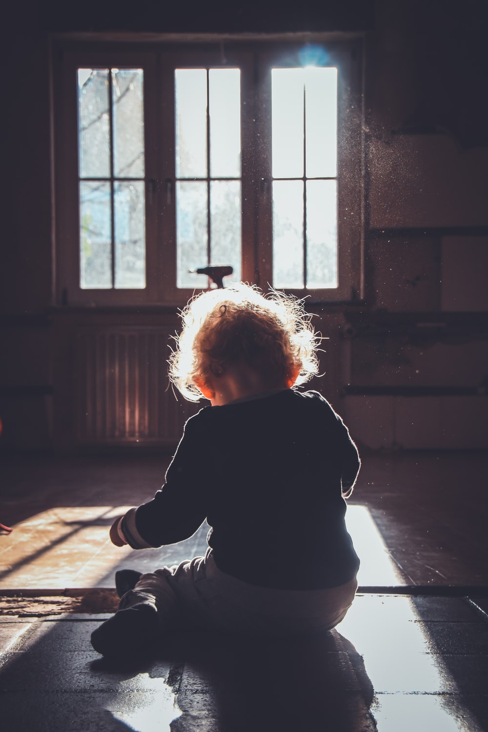 toddler sitting on brown wooden floor