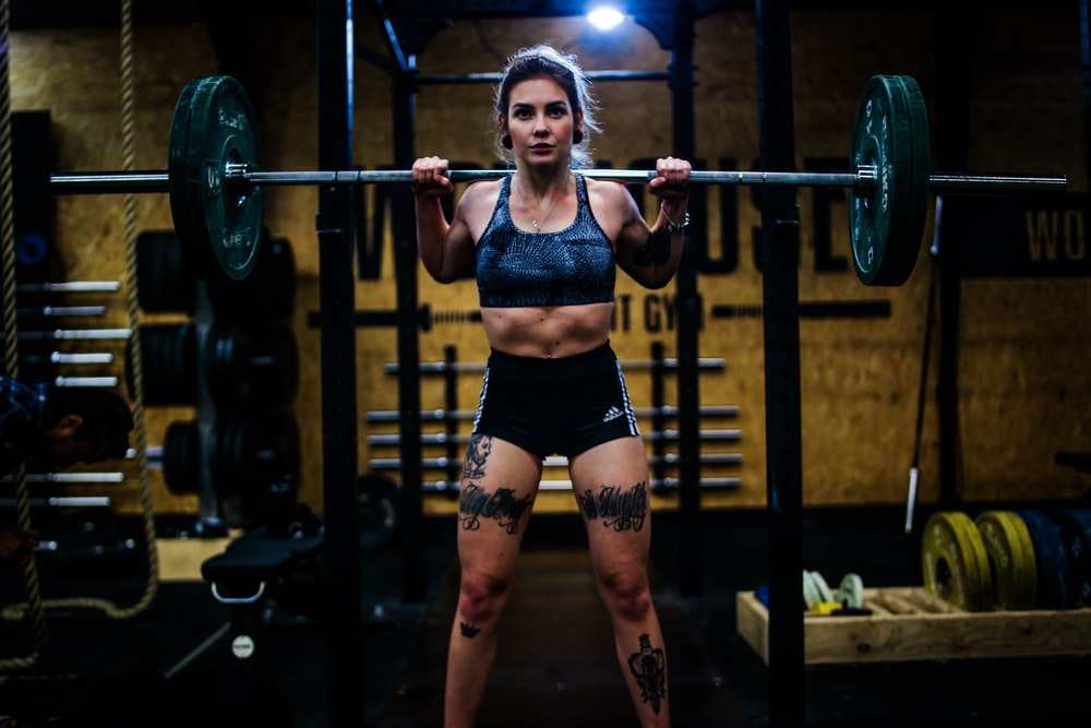 woman standing and carrying barbell