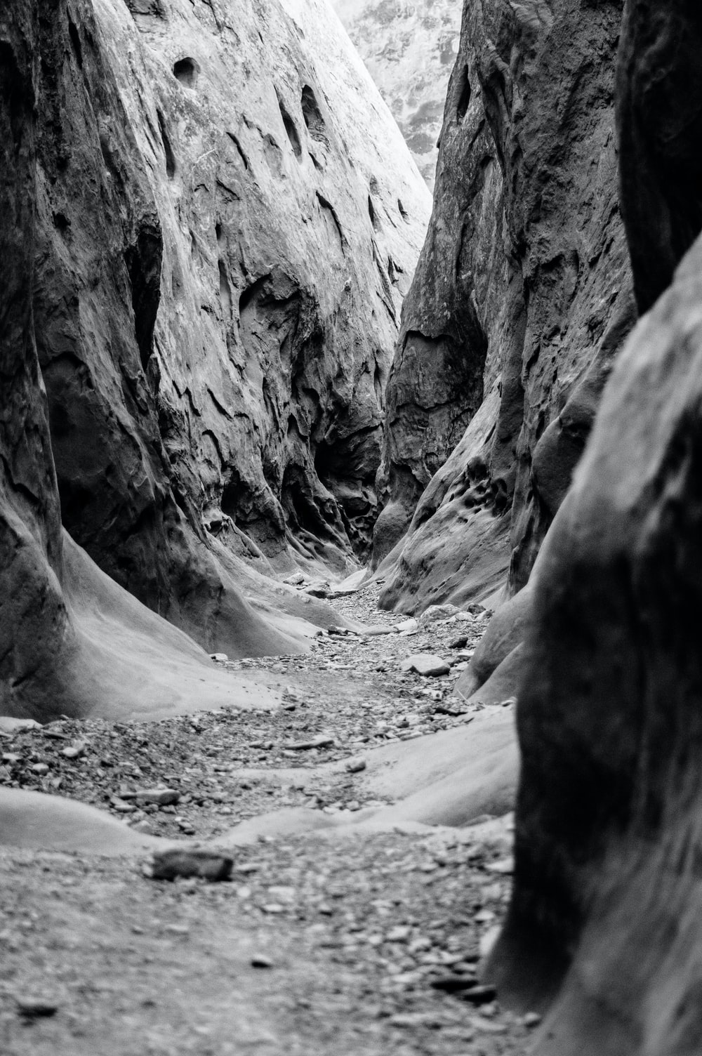 grayscale photo of pathway in middle of hills
