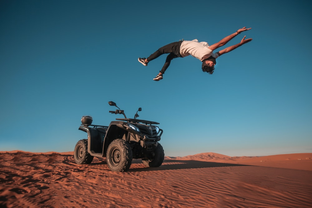 man backflipping on gray sand