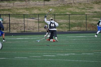 people playing on lacrosse inside green field team sport teams background