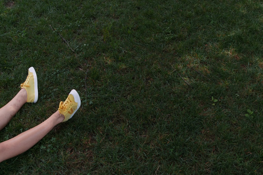 person in yellow shoes on grass