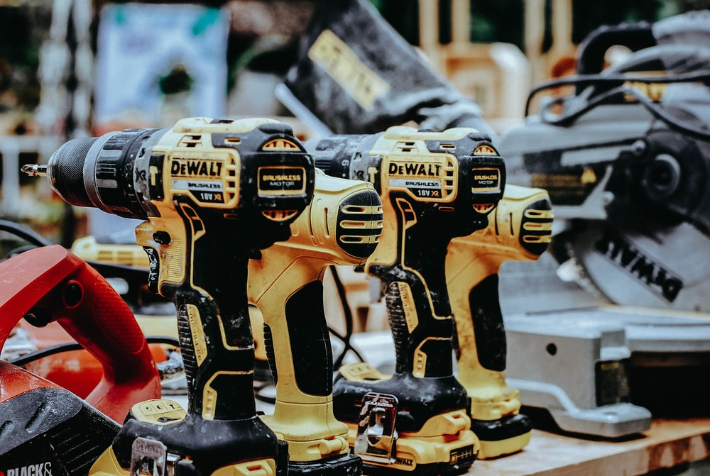 yellow Dewalt hand drills on table