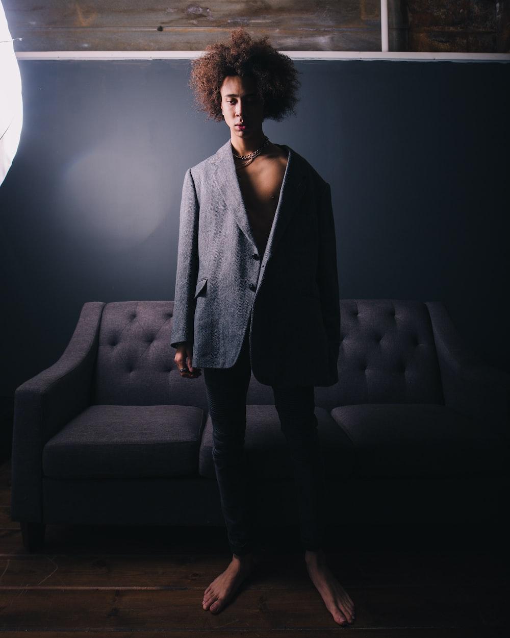 man standing wearing black blazer behind sofa