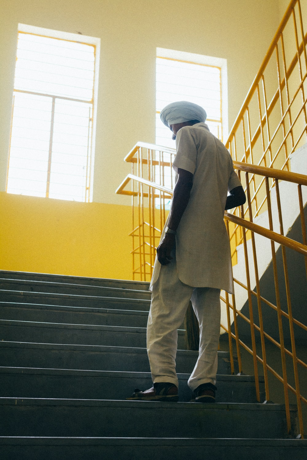 man in black jacket and gray pants standing on yellow staircase