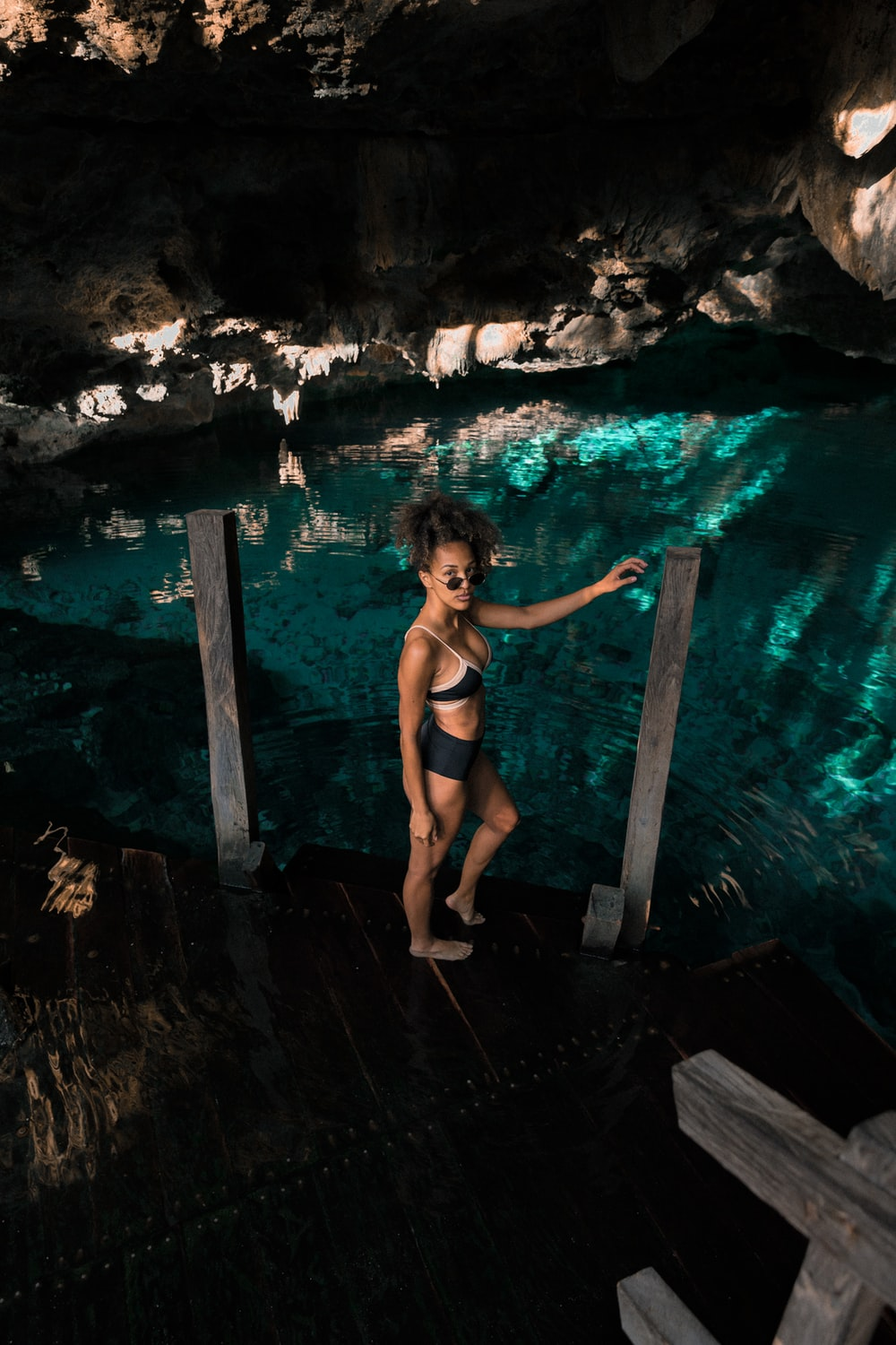 woman standing on wooden dock inside cave