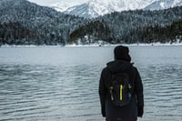 man wearing jacket and backpack facing body of water and mountain