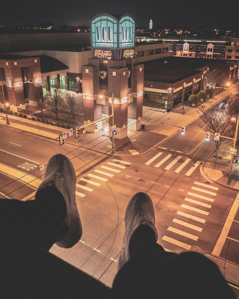 person sitting on top of building overlooking lighted street