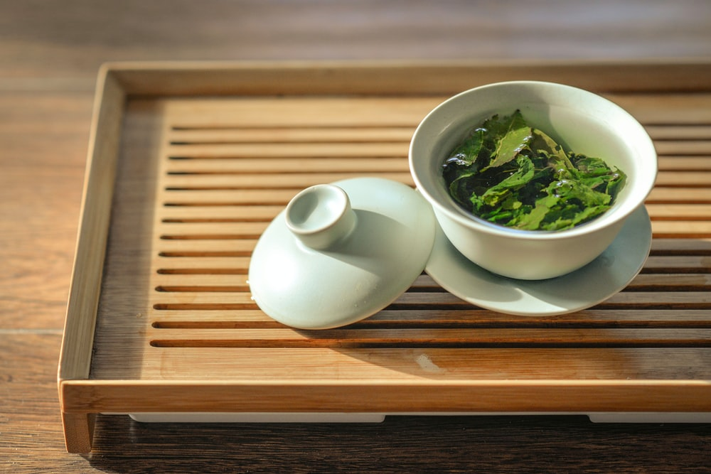 green tea leaves in white ceramic bowl with open lid