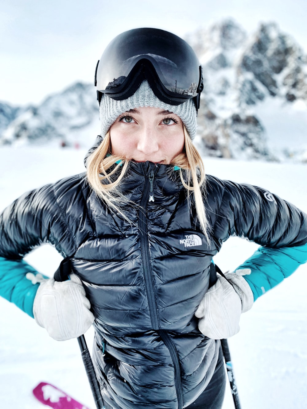 woman in The North Face bubble jacket with hand by her chest