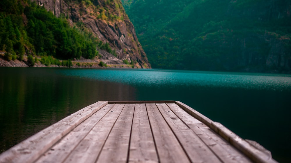 wooden dock facing body of water and mountain