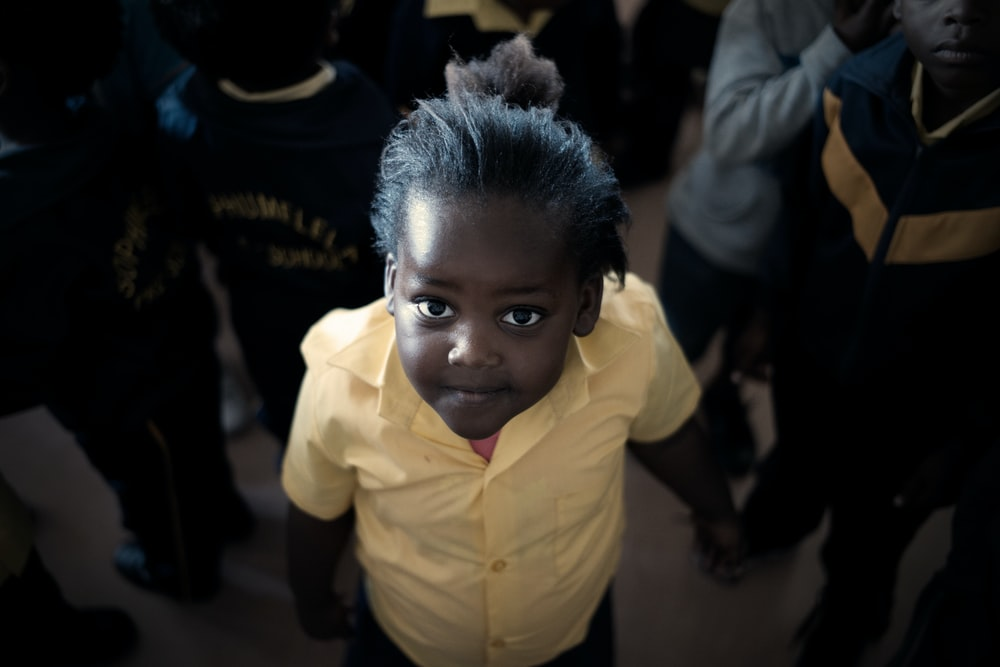 boy in yellow dress shirt surrounded by people