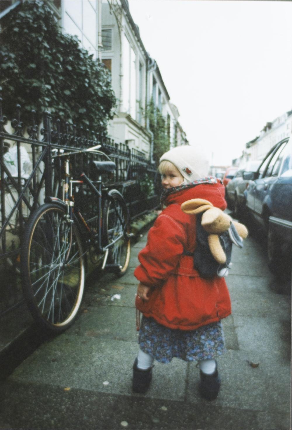 girl wearing red jacket near vehicles