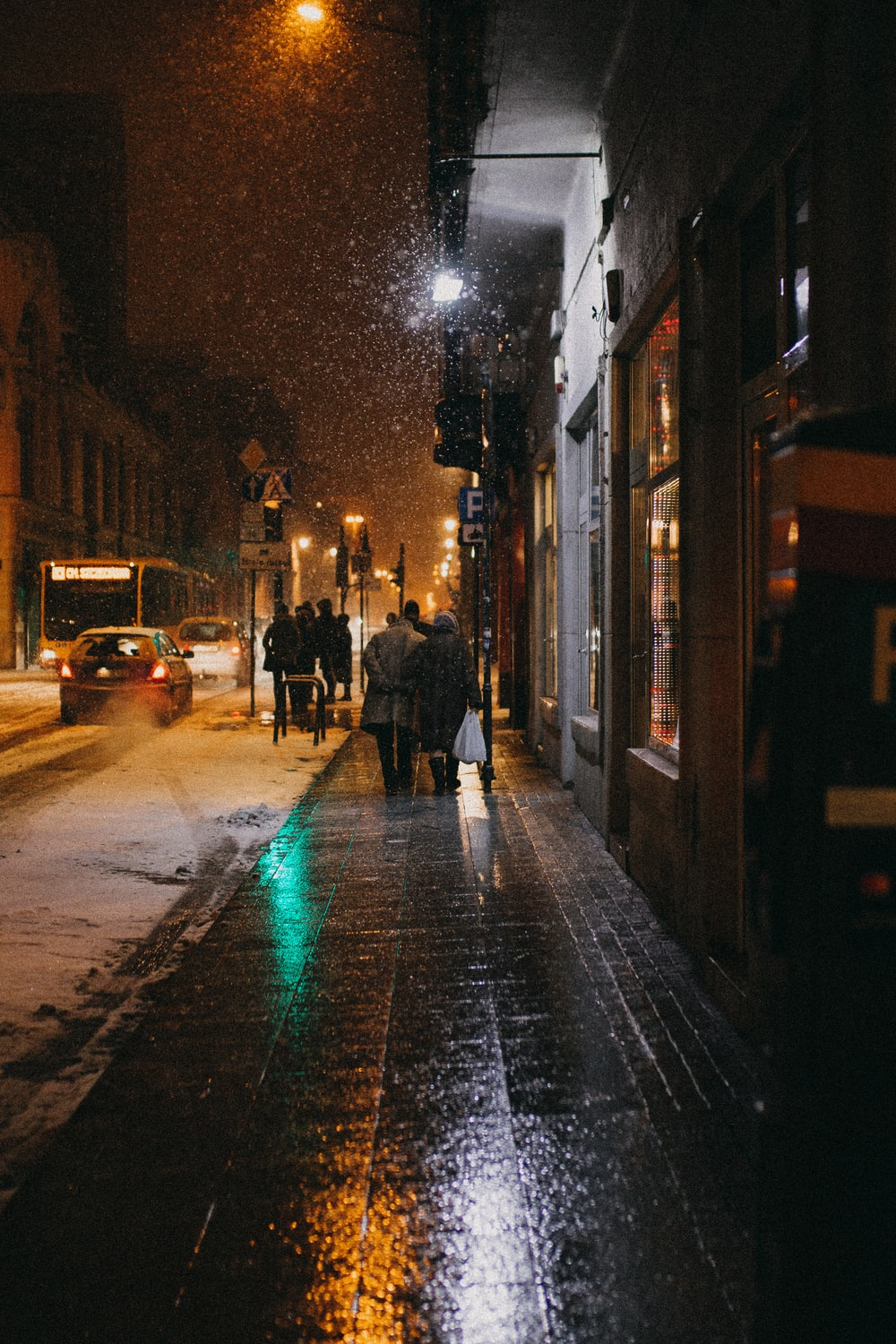 two person walking on sidewalk at night-time