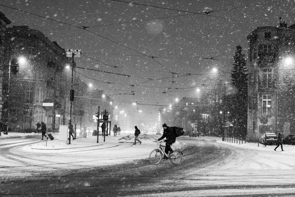 grayscale photography of person riding on bicycle