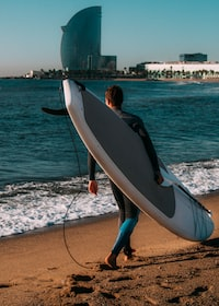 man carrying white and gray surfboard in the beach