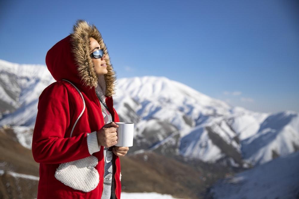 woman wearing red fur-trim hooded jacket holding white ceramic mug during daytime