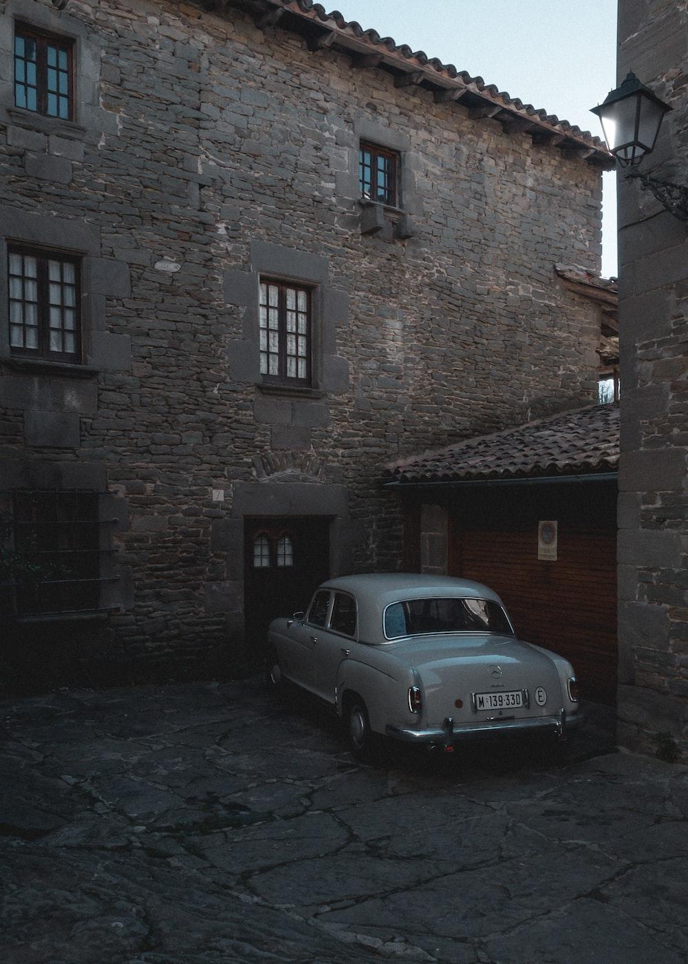 gray sedan parking in front of garage