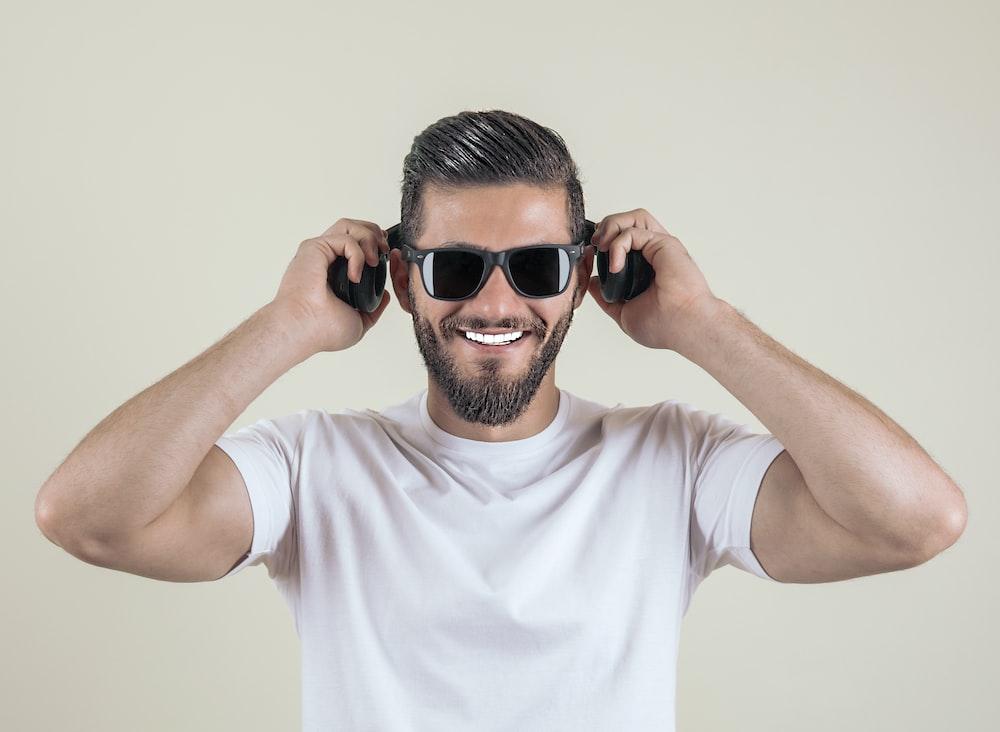 man wearing sunglasses and wireless headphones