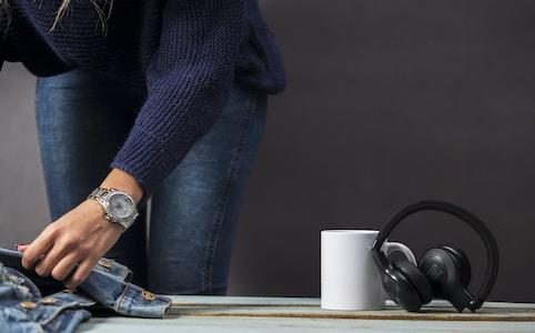 black JBL wireless headphones beside white ceramic mug