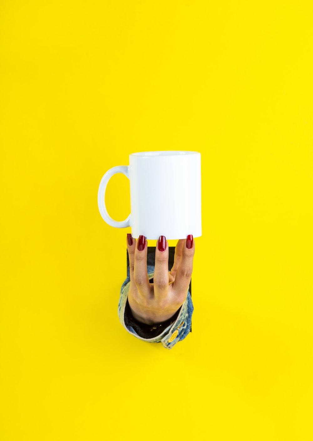 red nail polished hand holding white ceramic mug by fingertips