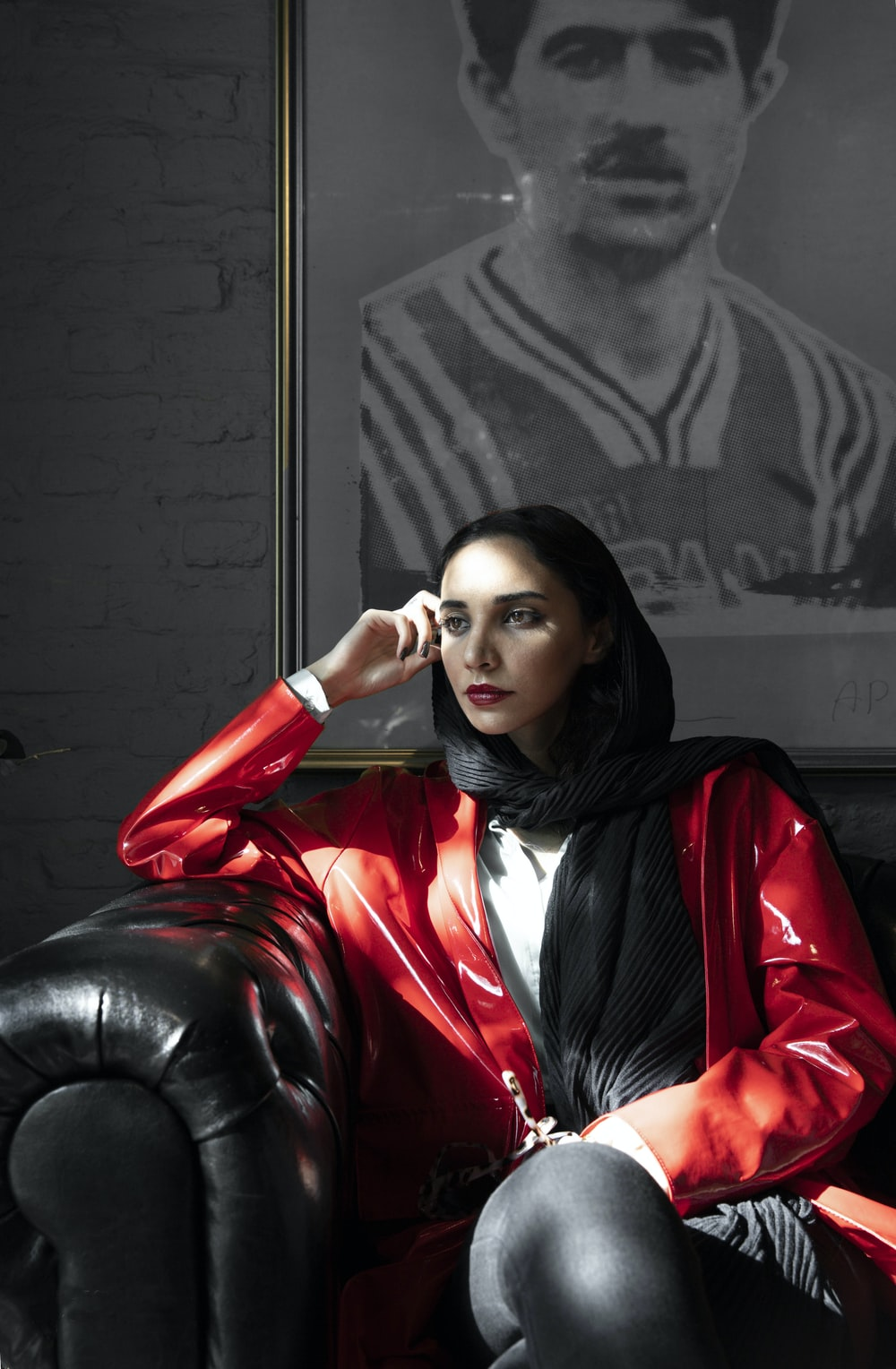 woman sitting on black sofa behind portriat on wall