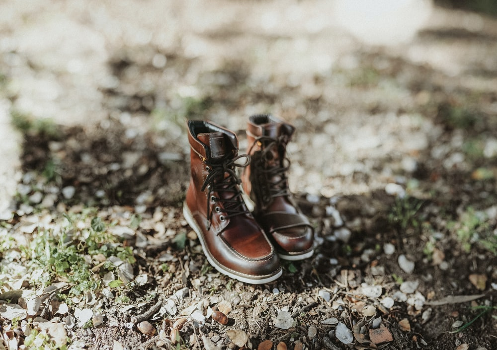 pair of brown leather boots on ground during daytime