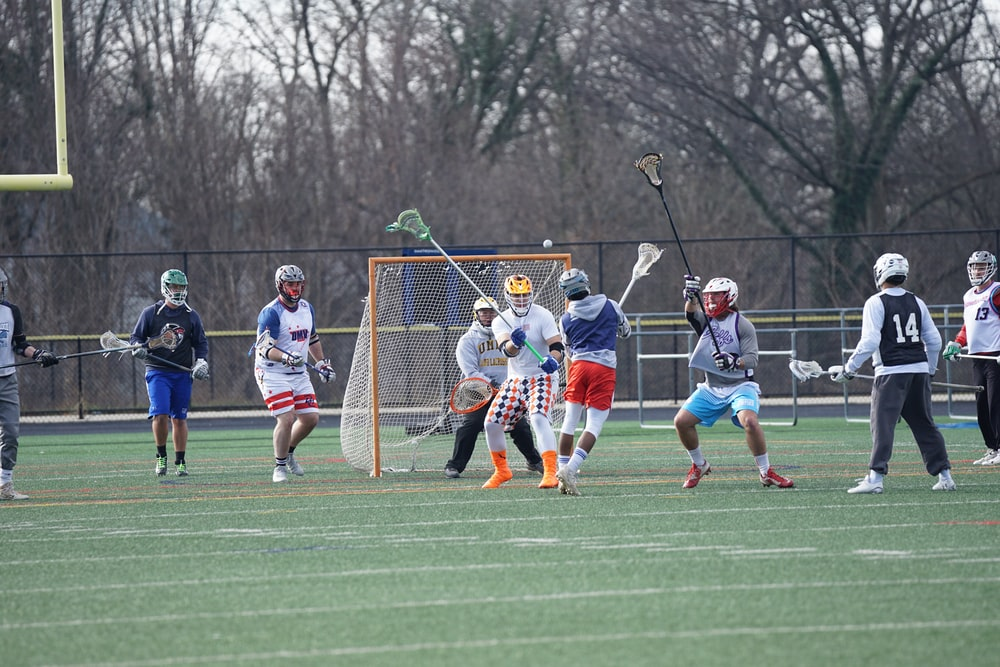 people playing lacrosse on field