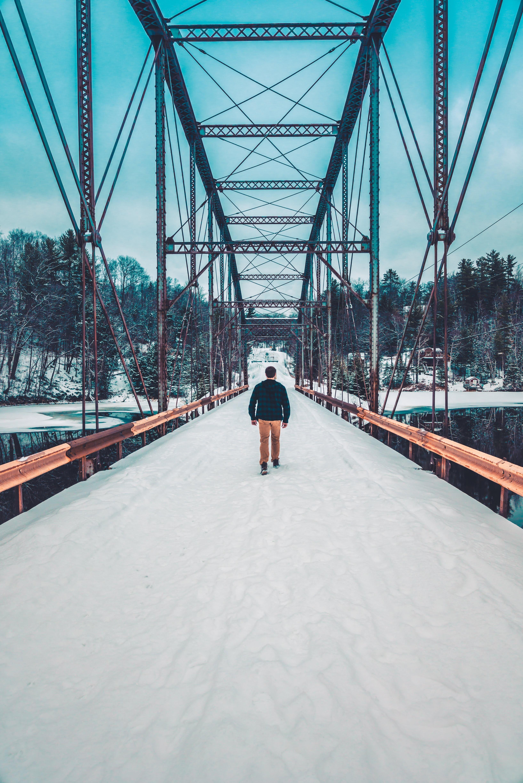 man walking on bridge during daytime