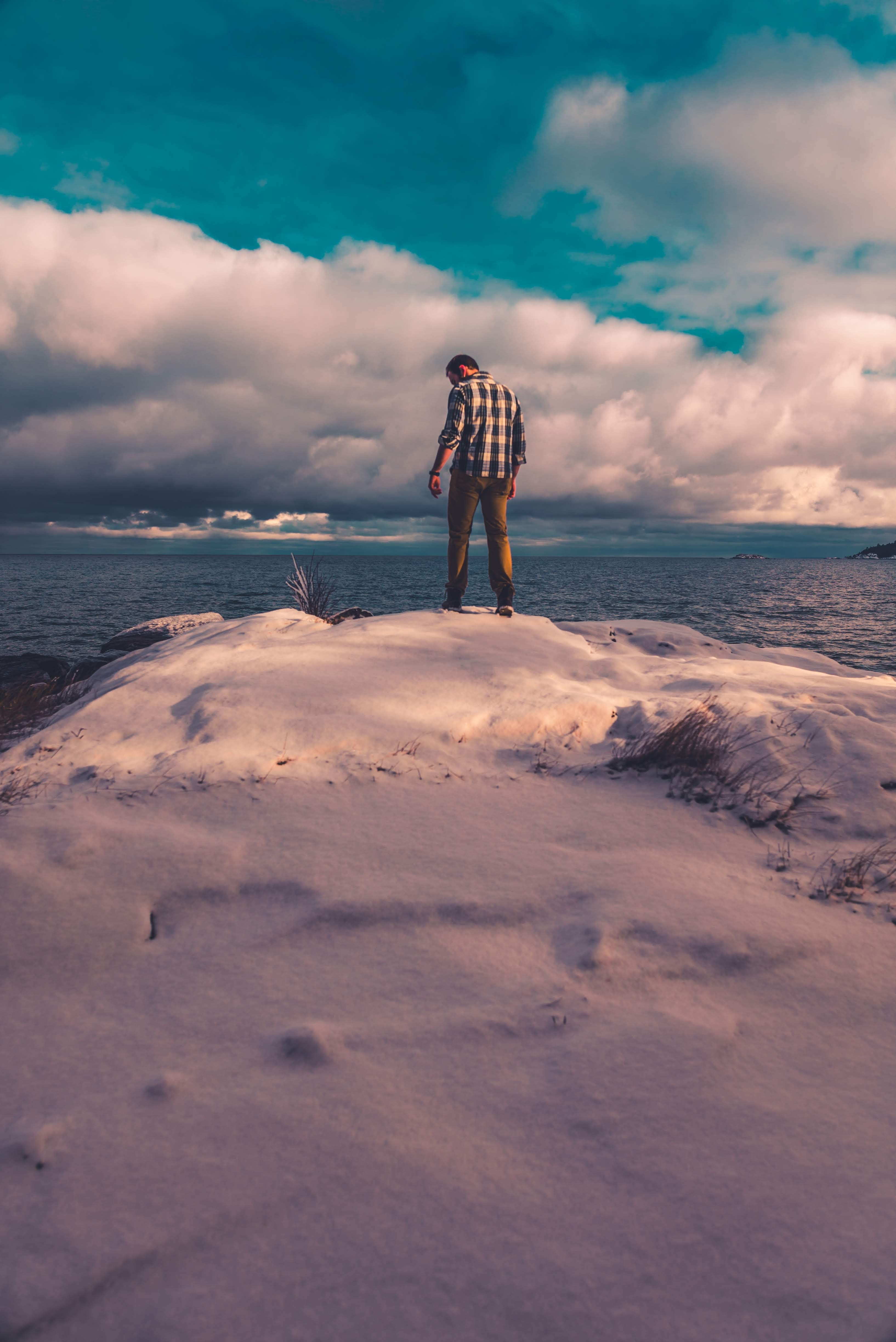 man standing on snow covered land while facing body of water