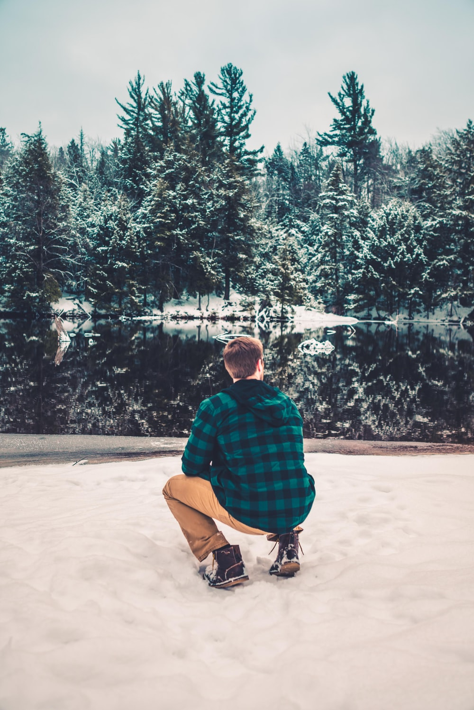 man sitting on snow field