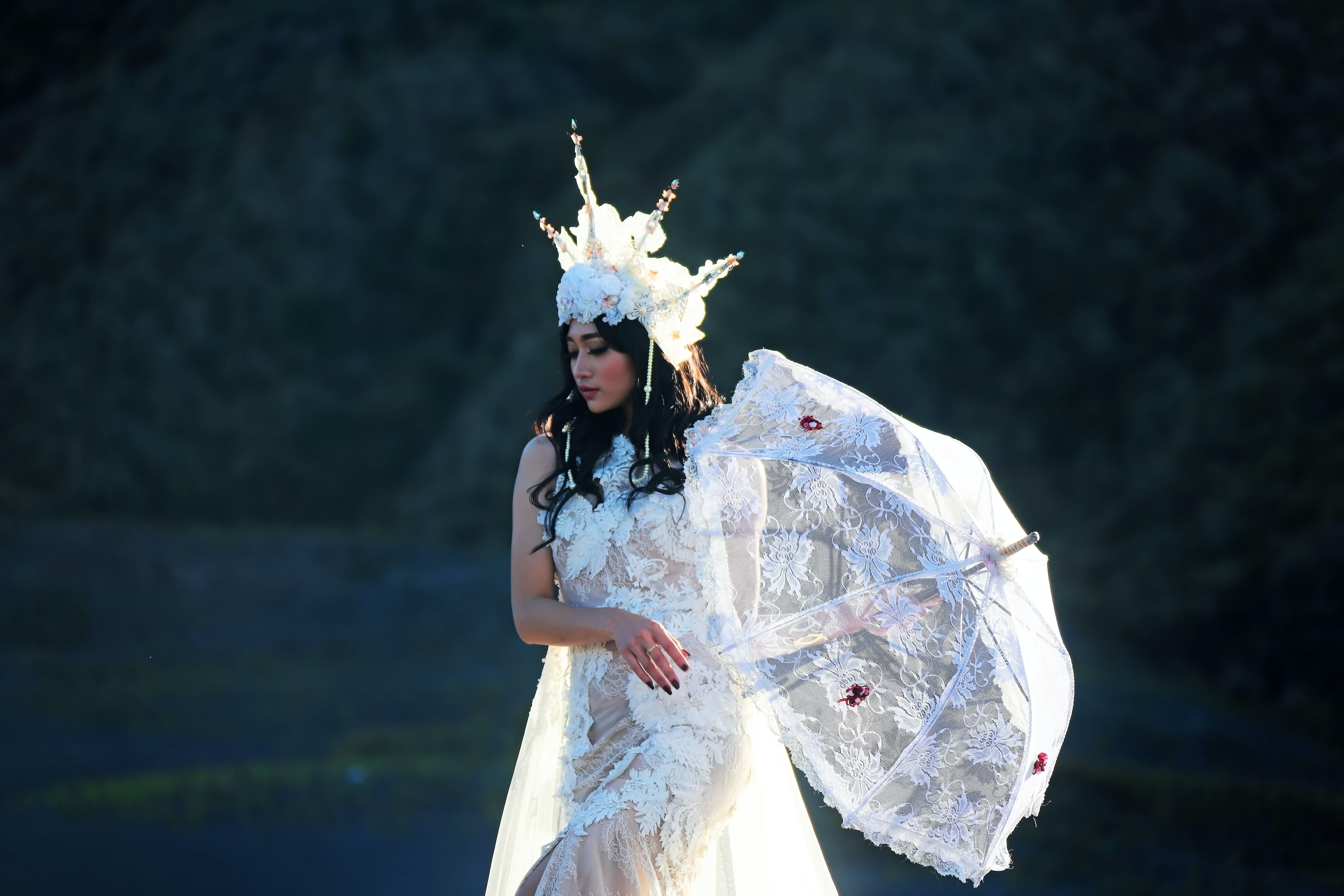 woman wearing white floral mesh gown with headdress and umbrella