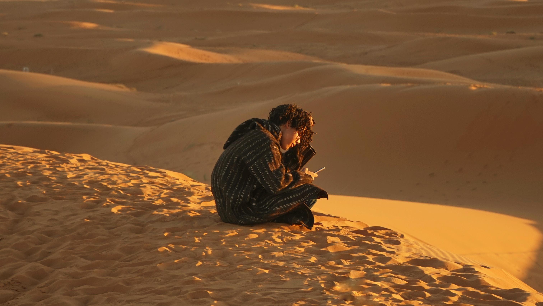 man sitting down on sand