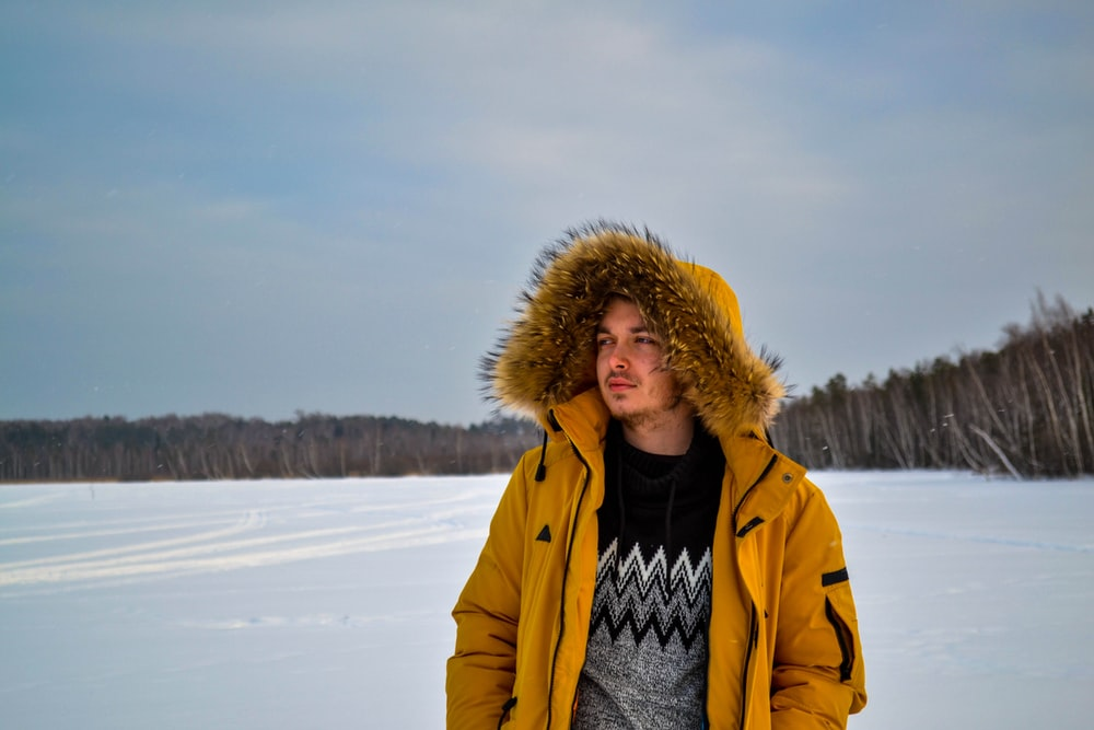 man wearing yellow pullover standing on snow field