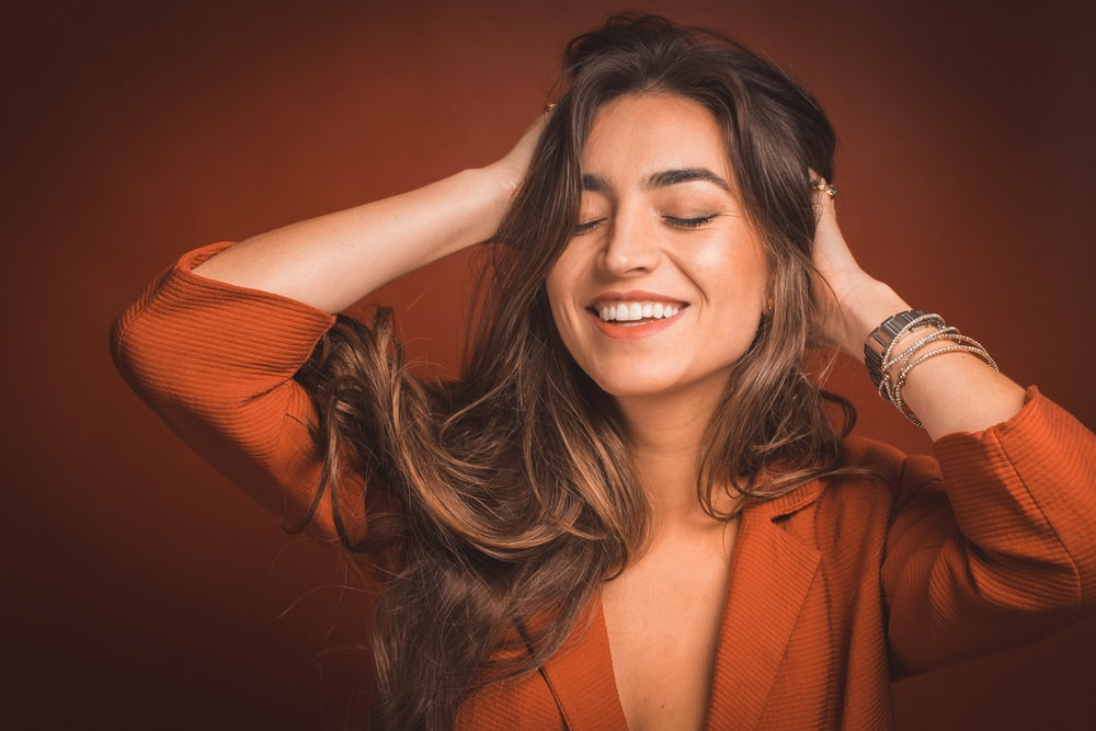 smiling woman in brown top holding hairs