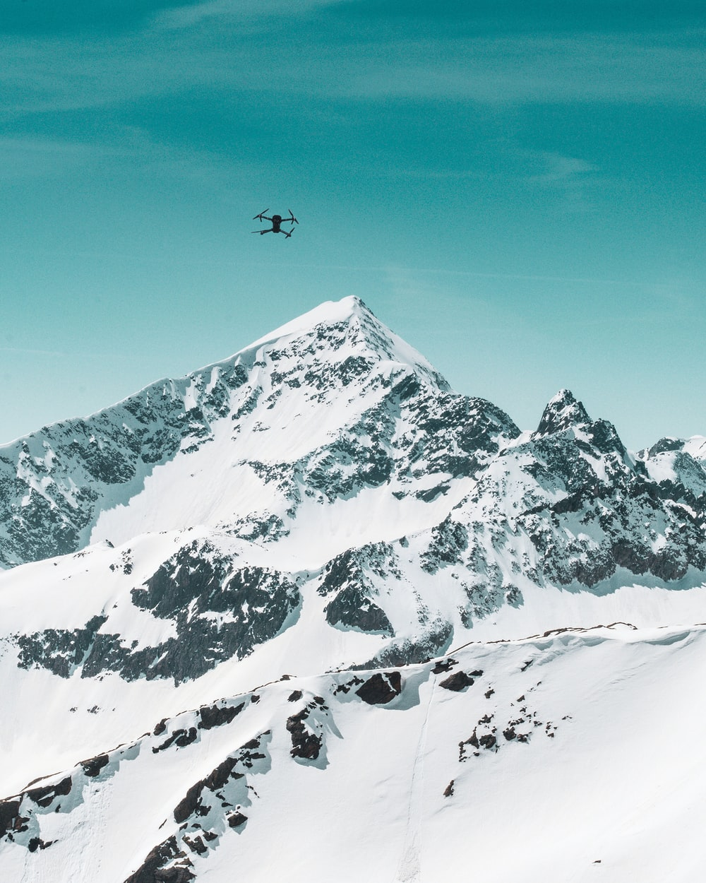 black quadcopter drone on air under mountain covered with snow