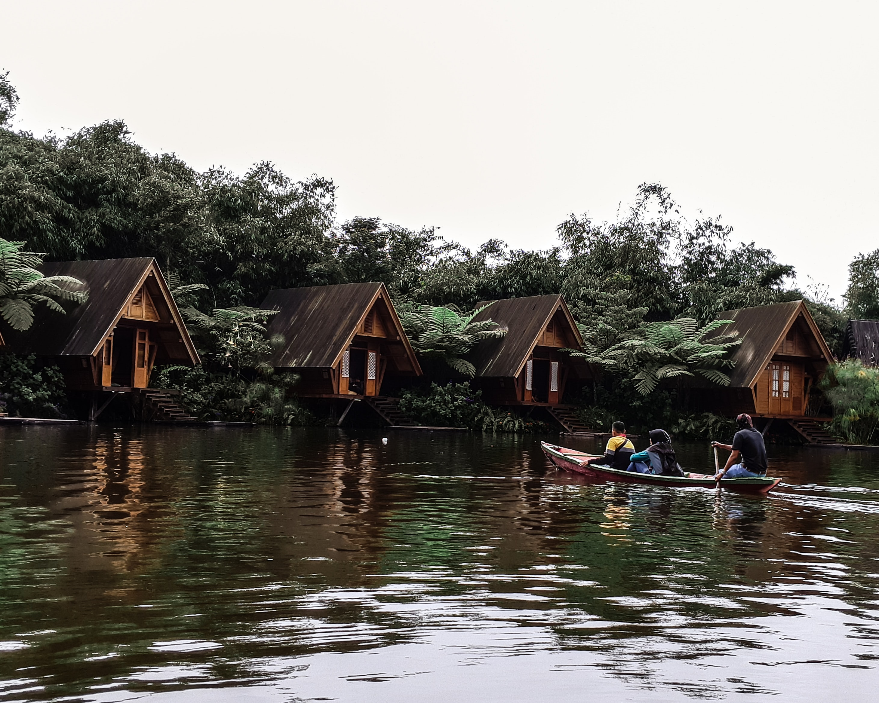 three men riding kayak on body of water leading to wooden cottages