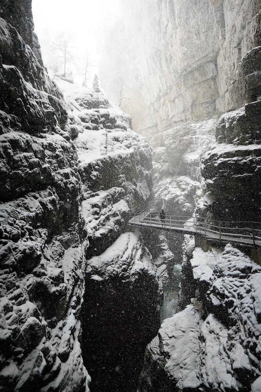 man standing on bridge in between rock formation