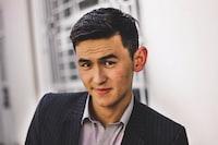 man in black blazer smiling by wall