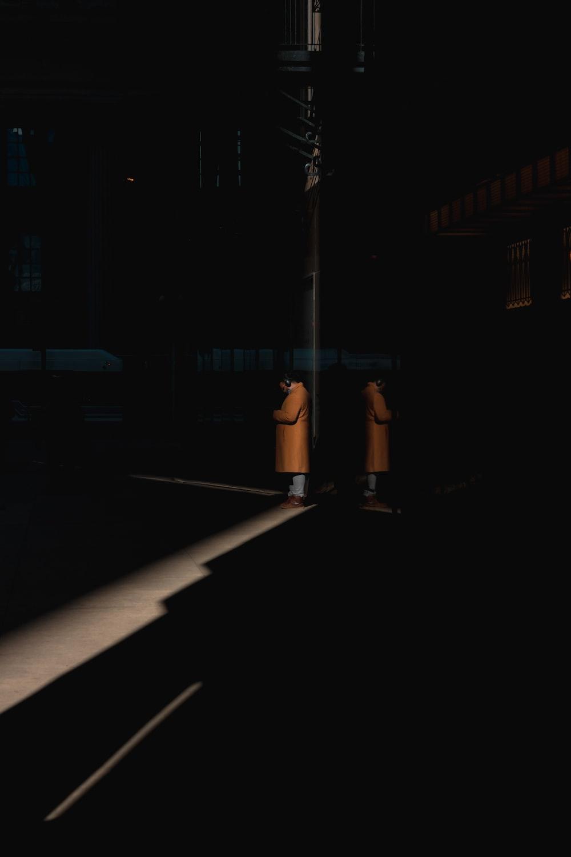 person in brown coat inside a dark room
