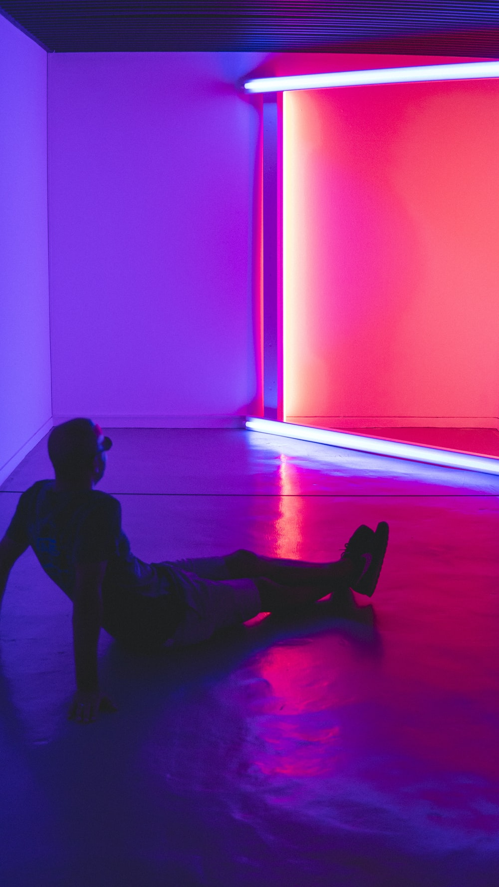 man sitting on floor facing a lighted room area