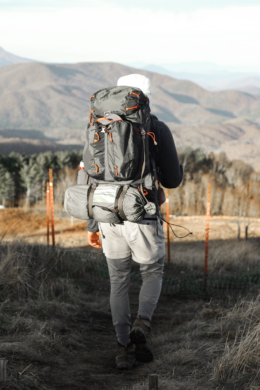 man walking near mountain hill during daytime