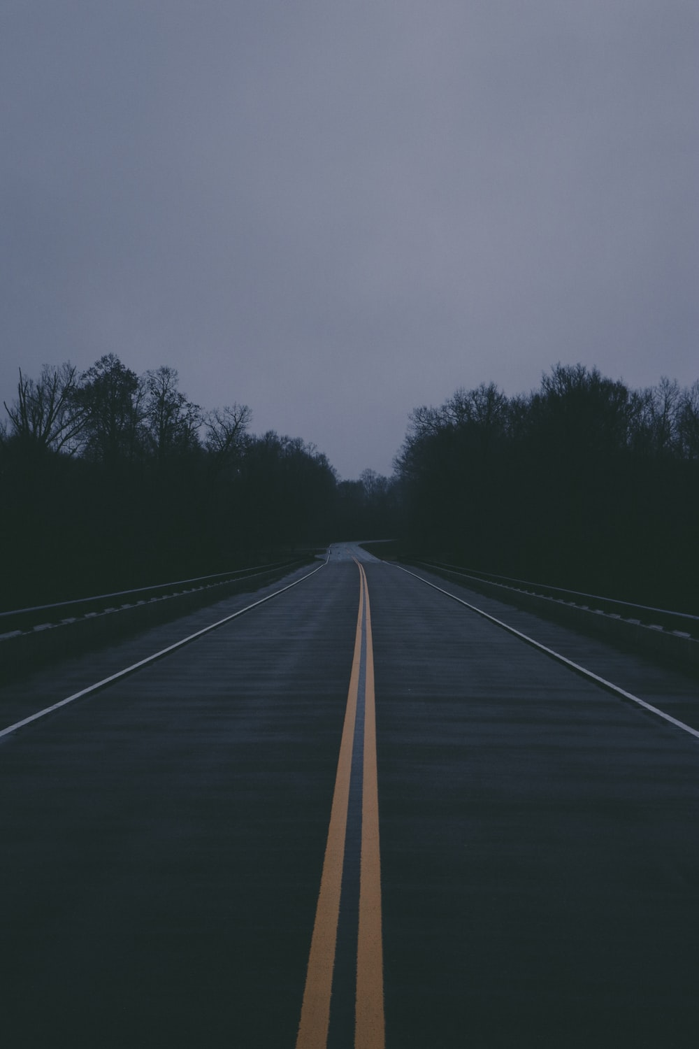 empty gray concrete road during nighttime