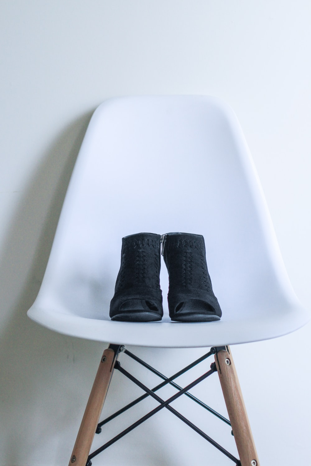 pair of black leather boots on white chair