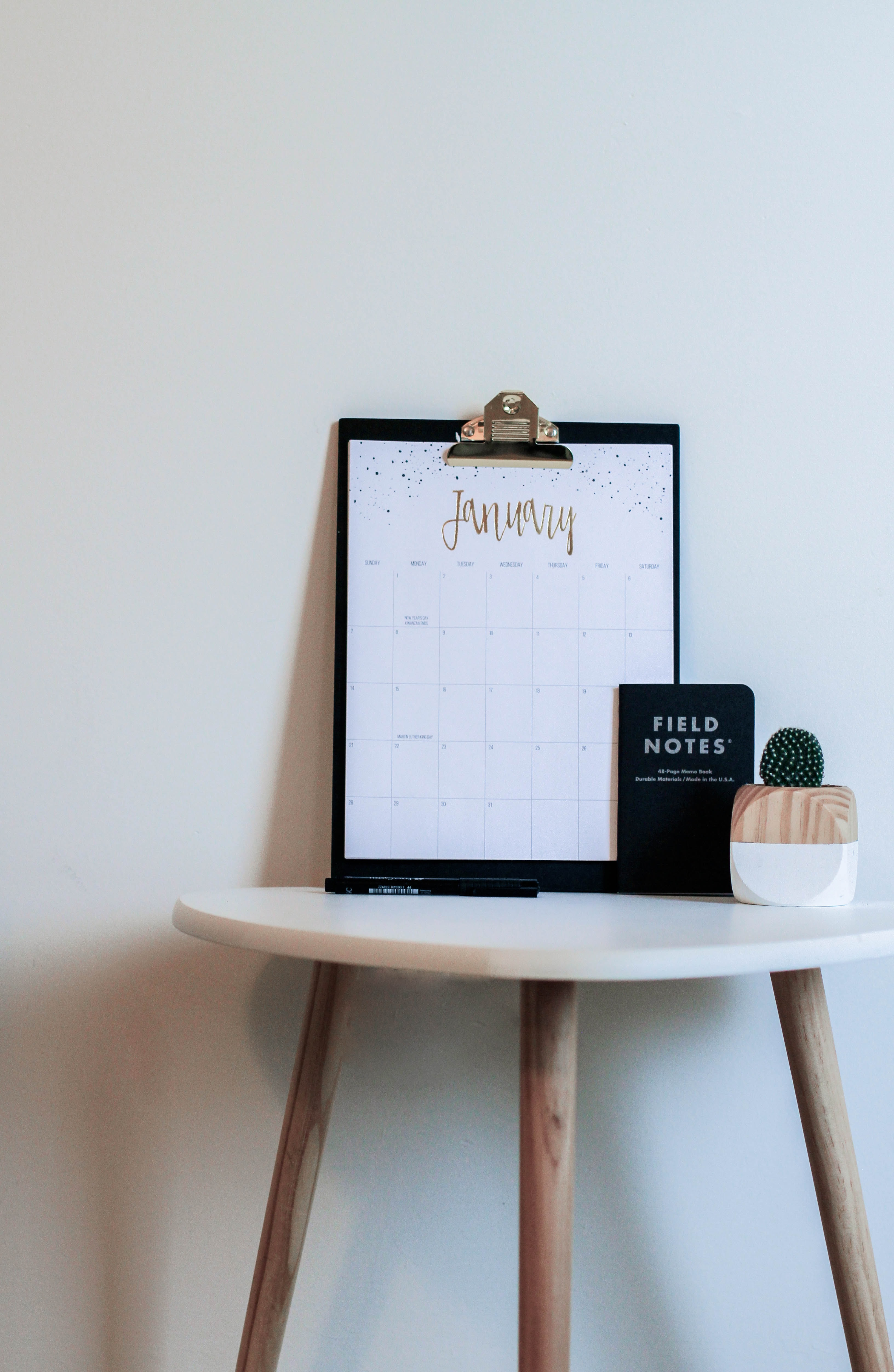 brown and white wooden table with black clipboard