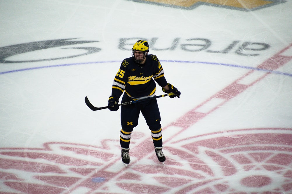 man in hockey gear holding stick on ice rink