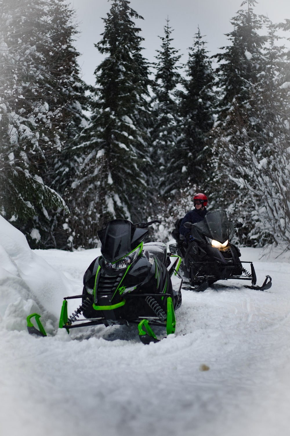green and black snowmobile beside black snowmobile during daytime