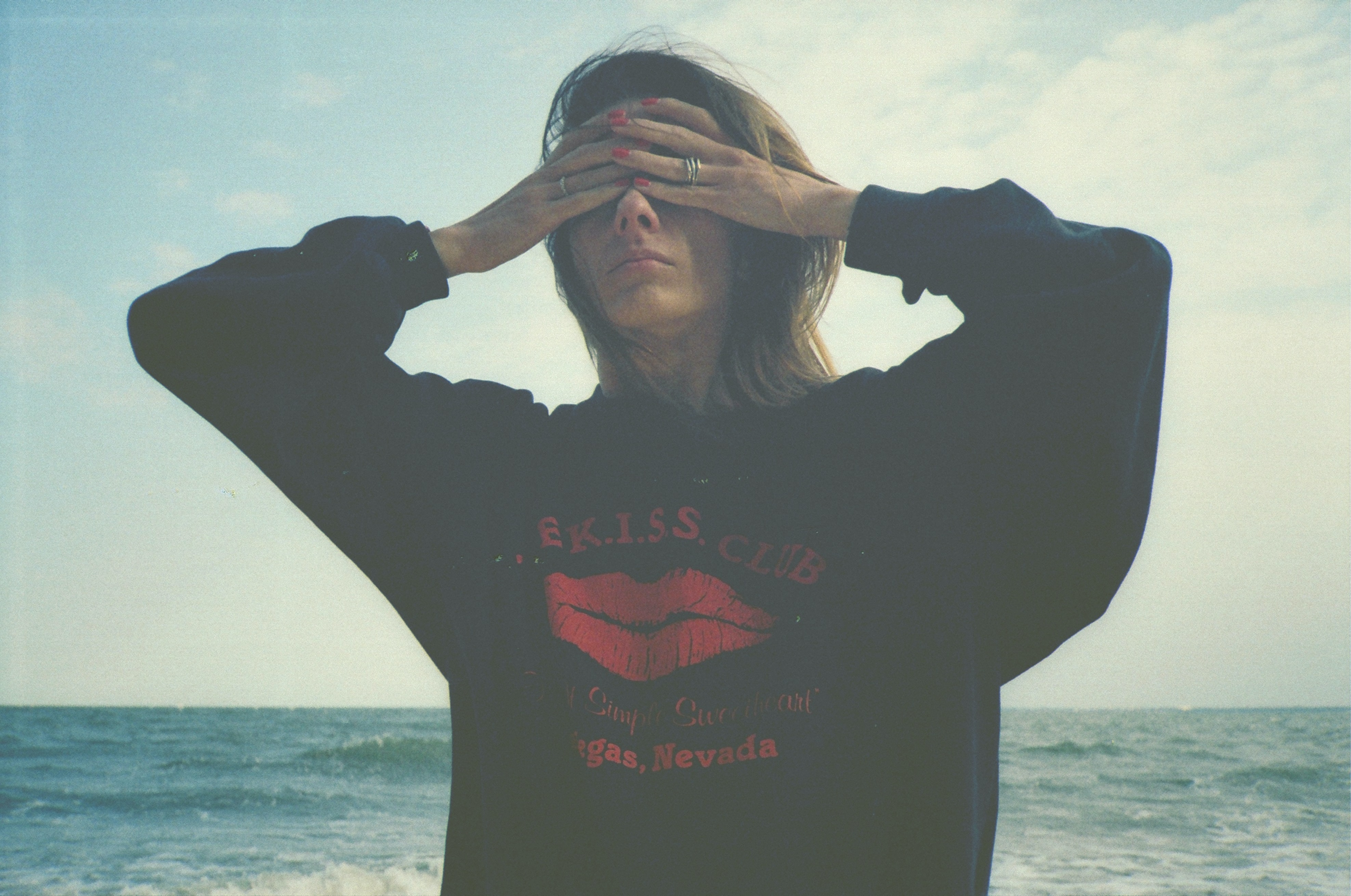 woman covering eyes by sea